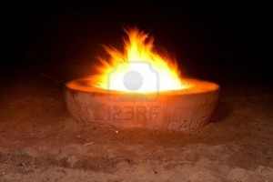 A blazing fire in a cement fire pit at the beach during night time. By Joe Belanger, via 123RF Stock Photos