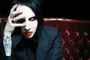 Photo of a man with straight black chin-length hair wearing pale white makeup, dark eyeliner, and bright red lipstick. His right hand is up and partially covering the right side of his face. He is wearing a black jacket and seated on a plush red sofa.